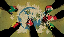 Hands covered with various national flags making jigsaw puzzle