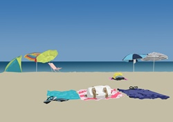 Sandy beach with towels and sunshades