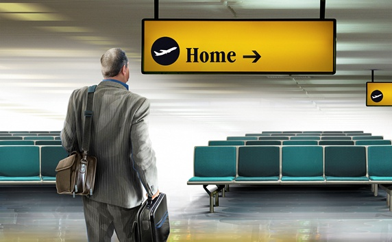 Businessman arriving in airport looking at home direction sign