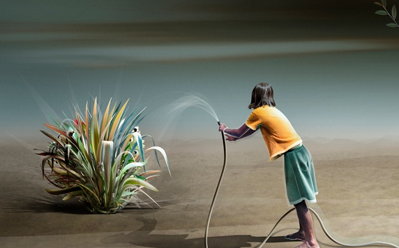 Teenage girl watering plant in desert