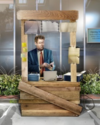 Businessman with laptop and mobile phone sitting in wooden office
