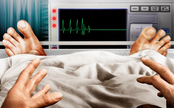 Frightened man in hospital bed seeing flatline pulse trace on monitor