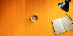 Overhead view of desk with cup of tea, pencil and blank note pad