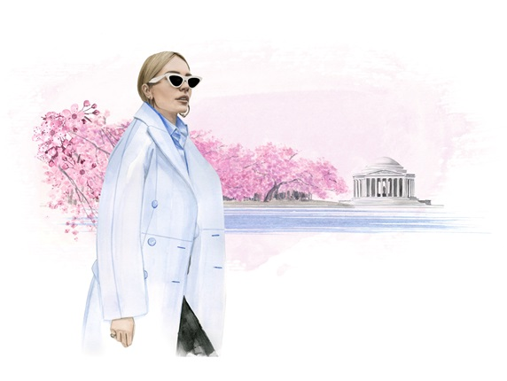 Elegant woman walking in front of blooming cherry trees and Jefferson Memorial