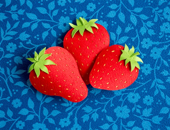 Paper strawberries on blue background