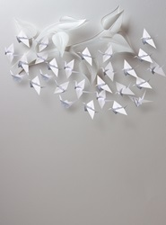 Origami paper cranes flying around twig with leaves