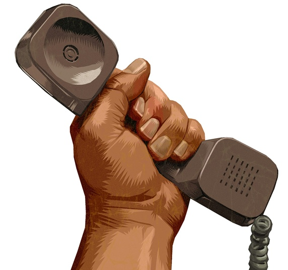 Man's hand raised, holding grey brown telephone handset