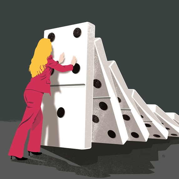 Woman in pink suit holding row of falling dominoes