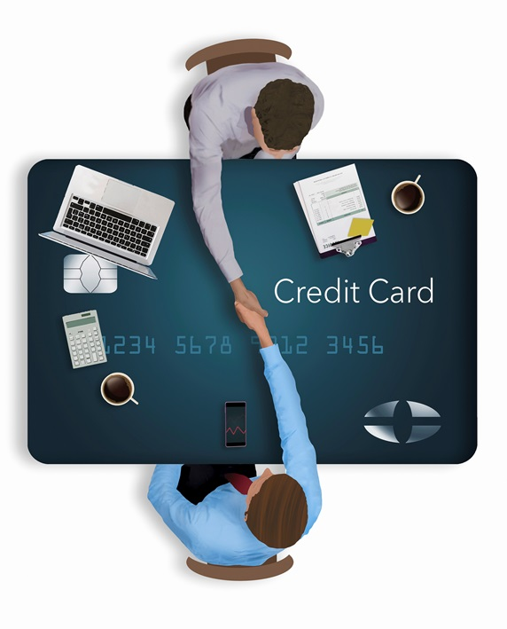 Overhead view of businessmen shaking hands over credit card desk