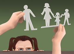 Girl looking at paper cut outs representing separated family