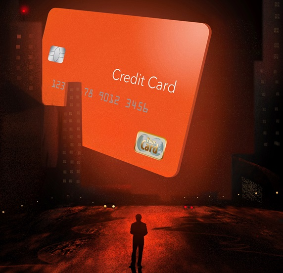 Silhouette of man facing large credit card in city at night