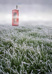 Red telephone booth in frozen field