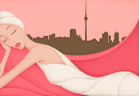 Beautiful woman wrapped in towels relaxing with view of city through window
