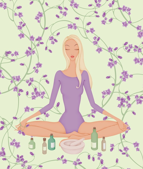 Woman sitting in lotus position with flowers and essential oils